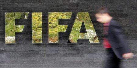 A man walks past a logo next to the main entrance of the Home of FIFA in Zurich