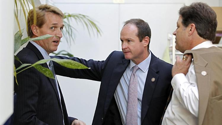 FILE - In this July 27, 2011, file photo Rep. Jeff Flake, R-Ariz., from left, Rep. John Sullivan, R-Okla., and Rep. Bill Shuster, R-Pa., confer in a hallway as Speaker of the House John Boehner tries to retool legislation to raise the nation's debt limit at the Capitol in Washington. Since his first House campaign a dozen years ago, Flake has worked diligently to cast himself as a conservative gadfly, willing to buck GOP leaders and even a Republican president. But a GOP primary opponent and Democrats are portraying him as a Washington insider, who should not get to succeed retiring Sen. Jon Kyl, R-Ariz., because he worked as a lobbyist 20 years ago for a Namibian uranium operation with ties to Iran. (AP Photo/J. Scott Applewhite, File)