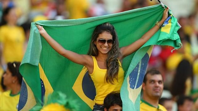 A fan of Brazil holds a national flag prior to the FIFA Confederations Cup Brazil 2013 Group A match between Brazil and Mexico at Castelao on June 19, 2013 in Fortaleza, Brazil.