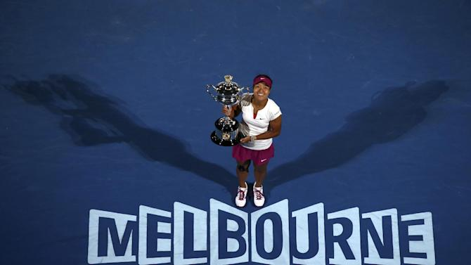 FILE - In this Jan. 25, 2014, file photo, Li Na, of China, holds the championship trophy after defeating Dominika Cibulkova, of Slovakia, in the women's singles final at the Australian Open tennis championship in Melbourne, Australia. Li formally announced her retirement on Friday, Sept. 19, 2014. (AP Photo/Eugene Hoshiko, File)