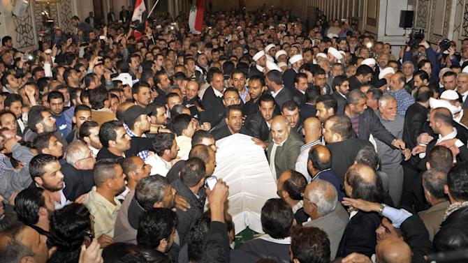 In this photo released by the Syrian official news agency SANA, mourners carry the body of Sheik Mohammad Said Ramadan al-Buti, an 84-year-old pro-government cleric during his funeral in the eighth century Omayyad Mosque, in Damascus, Syria, Saturday, March 23, 2013. Al-Buti, his grandson and scores of others were killed Thursday, March 21, 2013 when a suicide bomber detonated his explosives inside a mosque where al-Buti was giving a religious lesson. His assassination was a blow to Assad, who vowed Friday to avenge his death. (AP Photo/SANA)