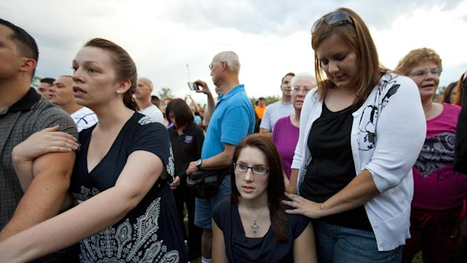 """Anne Marie Hochhalter, 30, bottom, and her friend Roxy Chesser, 30, second from right, attend a prayer vigil, held to remember the lost and injured in Friday's mass shooting at a movie theater, in a park outside the Aurora Municipal Center in Aurora, Colo., Sunday July 22, 2012. Hochhalter, a paralyzed victim of the Columbine High School tragedy over 12 years ago, and other survivors of the 1999 massacre reached out to people who survived the theater shooting. Twelve people were killed and dozens were injured in a shooting attack during a showing of the Batman movie, """"The Dark Knight Rises."""" Police have identified the suspected shooter as James Holmes. (AP Photo/Barry Gutierrez)"""