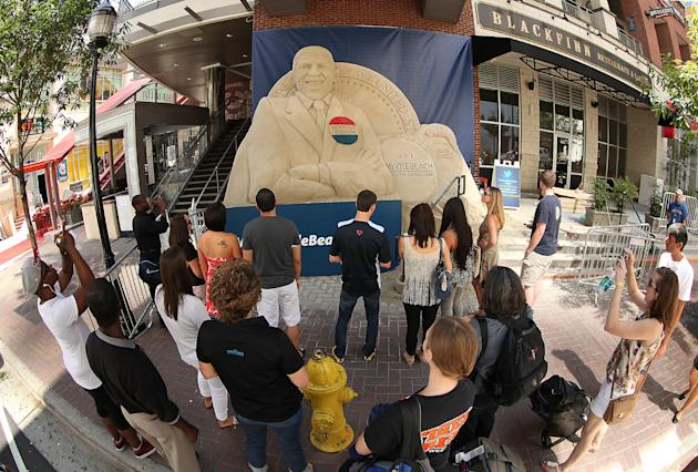 IMAGE DISTRIBUTED FOR VISITMYRTLEBEACH.COM - In this photograph taken by AP Images for VisitMyrtleBeach.com,  onlookers check out a 15.5 ton sand sculpture of President Barack Obama created by VisitMy