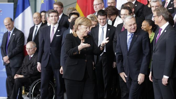 German Chancellor Angela Merkel, center, invites German and French ministers after a group photo for a meeting of both governments at the chancellery in Berlin, Tuesday, Jan. 22, 2013. The governments meet as part of events marking the 50th anniversary of the signing of the Elysee Treaty, a landmark accord cementing reconciliation between the two European powers. (AP Photo/Markus Schreiber)