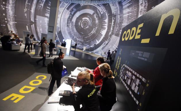 "Visitors look at the ""code_n - code of the new"" booth, a platform for 50 international start-ups at the CeBIT trade fair in Hanover"