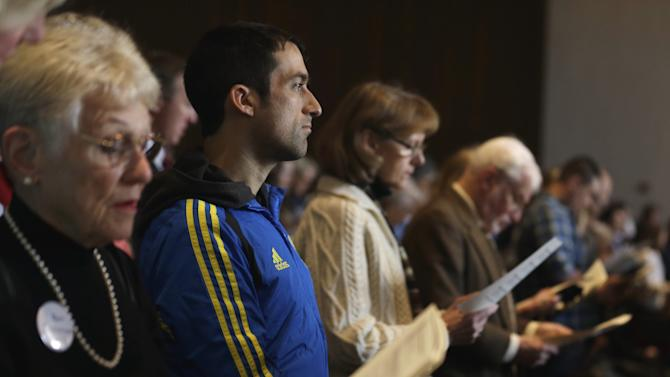 Wearing his Boston Marathon runner's jacket, David Delmar, 28, second from left, a member of Trinity Episcopal Church in Boston, attends a service at Temple Israel, which allowed the Trinity congregation to hold their service, Sunday, April 21, 2013, in Boston. Trinity is within the blocked-off area near the finish line of the Boston Marathon, where earlier in the week two bombs exploded. Delmar, who finished the marathon about 30 minutes before the explosions, was running his first marathon as part of charity to Trinity. (AP Photo/Julio Cortez)