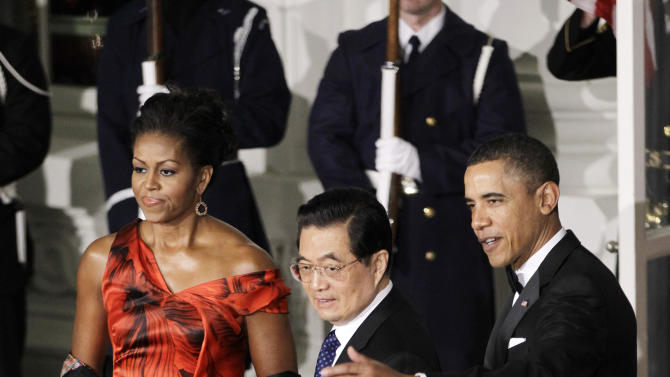 FILE - In this Jan. 19, 2011 file photo, President Barack Obama and first lady Michelle Obama welcome China's President Hu Jintao to the North Portico of the White House in Washington for the State Dinner. America's stature has taken a hit in Japan since the 2008 financial meltdown, which highlighted the excesses of U.S.-style capitalism to many Japanese. They also fret about the increased attention Washington is giving China, which supplanted Japan as the world's second-largest economy. (AP Photo/Charles Dharapak, File)