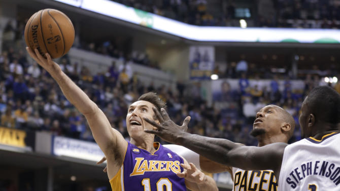 Los Angeles Lakers guard Steve Nash, left, shoots and scores next to Indiana Pacers forward David West (21) and guard Lance Stephenson during the first half of an NBA basketball game in Indianapolis, Friday, March 15, 2013. (AP Photo/Michael Conroy)