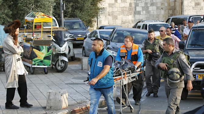 Israeli rescue workers transport the body of a Palestinian who stabbed members of the Israeli police before he was shot dead outside Jerusalem's Old City