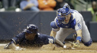 Milwaukee Brewers' Nyjer Morgan, left, slides safely past Los Angeles Dodgers catcher A.J. Ellis during the 10th inning of a baseball game on Wednesday, April 18, 2012, in Milwaukee. The Brewers won 3-2. (AP Photo/Morry Gash)