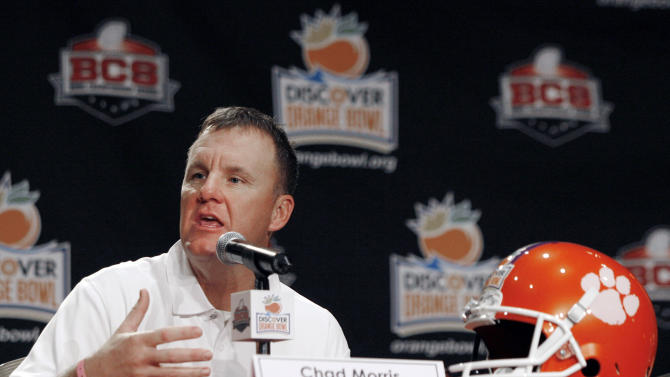 FILE - In this Dec. 31, 2011, file photo, Clemson offensive coordinator Chad Morris speaks to reporters during an NCAA college football news conference in Fort Lauderdale, Fla. Salaries for coordinators continue to rise in the ACC, as they do around college football. But Clemson has taken it to a new level. The defending Atlantic Coast Conference champions are paying a combined $2.1 million this season for their coordinators. Second-year offensive leader Chad Morris is the highest paid assistant in college football at $1.3 million a year. (AP Photo/Jeffrey M. Boan, File)