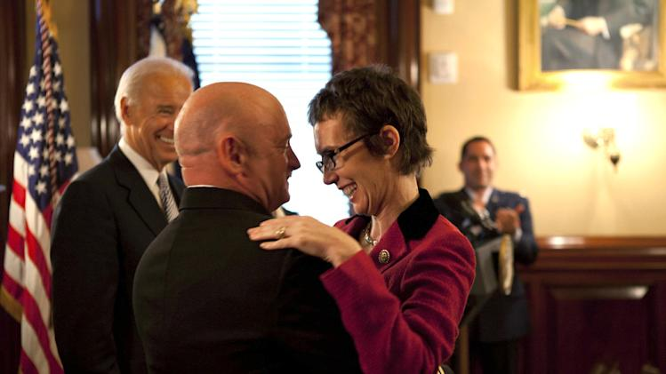In this image released by the White House, Navy Capt. Mark Kelly hugs his wife Rep. Gabrielle Giffords, D-Ariz., after he received the Legion of Merit from Vice President Joe Biden during Kelly's retirement ceremony in the Secretary of War Suite in the Eisenhower Executive Office Building on the White House complex in Washington, Thursday, Oct. 6, 2011. (AP Photo/The White House, David Lienemann)