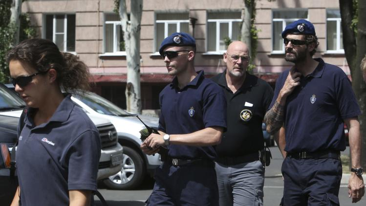 Members of the Dutch police mission walk after returning to Donetsk