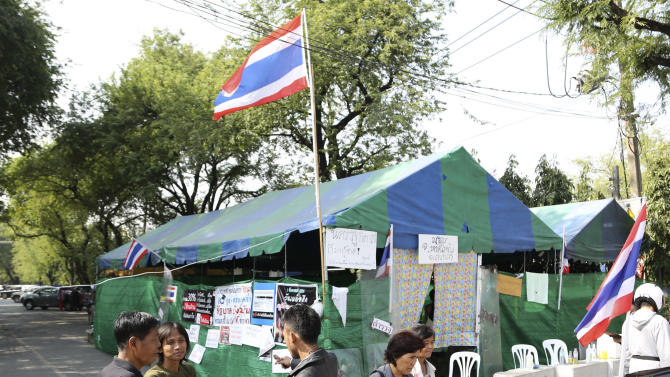Thai anti-government protesters chat outside a makeshift camp where their colleagues were shot outside the prime minister's office of Government House, Saturday, Dec. 28, 2013 in Bangkok, Thailand. Gunmen killed an anti-government protester and wounded two others in the Thai capital on Saturday, raising fears that the country's deepening political crisis was headed toward sustained violence on the streets of Bangkok. (AP Photo/Apichart Weerawong)