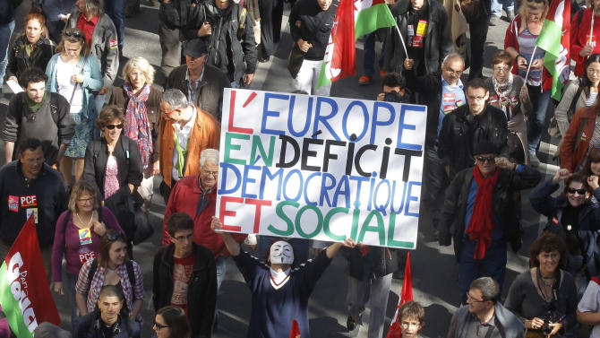"A demonstrator holds a placard which reads: ""Europe in Social and Democratic Deficit"" during a rally to protest against the austerity measures announced by the French government, in Paris, Sunday, Sept. 30, 2012. (AP Photo/Michel Euler)"