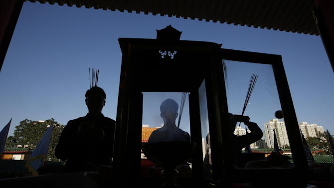 Chinese pray during the celebration of the Lunar New Year at a temple in Hong Kong, Monday, Feb. 8, 2016. The celebration marks the Year of the Monkey in the Chinese calendar. (AP Photo/Kin Cheung)
