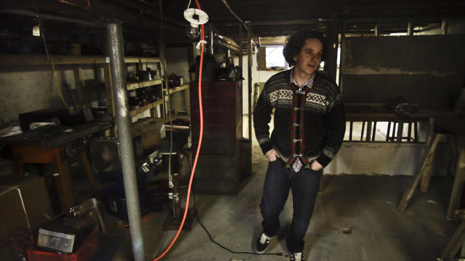 Coke Wisdom O'Neal, an artist who photographs is creations, walks through the basement of his Red Hook studio that was damaged in Superstorm Sandy, Monday, Dec. 3, 2012 in New York.  (AP Photo/Bebeto Matthews)
