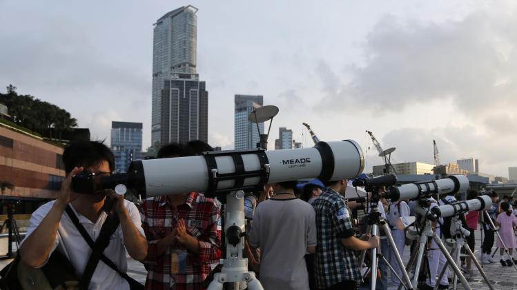 Hong Kong stargazers use telescopes to observe the transit of Venus along the Victoria Habour in Hong Kong Wednesday, June 6, 2012. From the U.S. to South Korea, people around the world turned their attention to the daytime sky on Tuesday and early Wednesday in Asia to make sure they caught the rare sight of the transit of Venus. The next one won't be for another 105 years. (AP Photo/Vincent Yu)