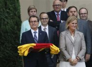 """Catalonia's regional president Artur Mas (L) holds a regional flag surrounded by local politicians during ceremony to mark the """"Diada de Catalunya"""" (Catalunya's National day) in central Barcelona September 11, 2013. REUTERS/Gustau Nacarino"""