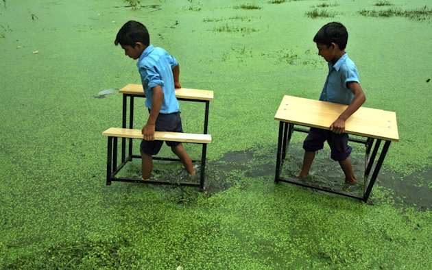 Primary school boys carry their benches after their school was flooded due to heavy rains at Bassi Kalan village