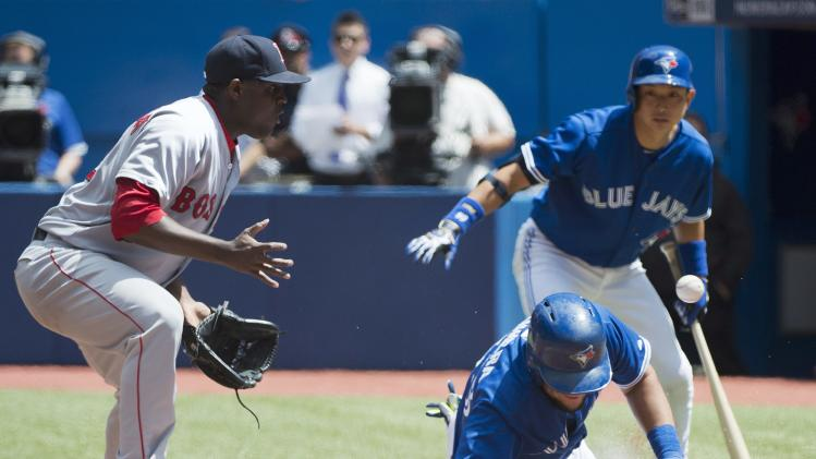 Toronto Blue Jays' Melky Cabrera, right, slides safely home past Boston Red Sox starting pitcher Rubby De La Rosa, left, after a passed ball during first inning baseball action in Toronto on Thursday, July 24, 2014. Blue Jays' Munenori Kawasaki, rear, watches the play. (AP Photo/The Canadian Press, Nathan Denette)