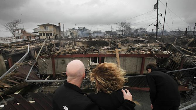 FILE - In this Tuesday, Oct. 30, 2012, file photo, Robert Connolly, left, embraces his wife Laura as they survey the remains of the home owned by her parents that burned to the ground in the Breezy Point section of New York, during Superstorm Sandy.  In Google's 12th annual roundup of trending searches, Superstorm Sandy, the damaging storm that knocked out power and flooded parts of the East Coast in the midst of a U.S. presidential campaign, was third. (AP Photo/Mark Lennihan, File)