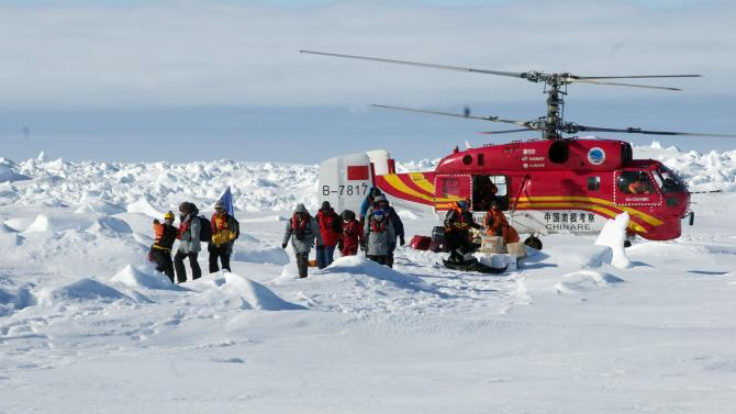 A helicopter from the Xue Long Chinese icebreaker unloads rescued passengers from the ice-bound Russian ship, Akademik Shokalskiy, in East Antarctica, in this handout courtesy of Fairfax's Australian Antarctic Division