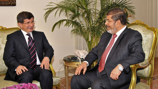 """In this image released by the Egyptian President, Egyptian President Mohammed Morsi, right, meets with  Turkish Foreign Minister Ahmet Davutoglu at the Presidential Palace in Cairo, Egypt, Monday, Sept. 17, 2012.  Turkey, which hosts some 80,000 Syrian refugees, has accused Syria of """"state terrorism"""" and has allowed rebels to use its territory as a base. (AP Photo/Egyptian Presidency)"""