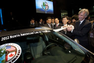 Hyundai Motor America CEO John Krafcik, right, and Hyundai President Seong Hyon Park, second from right, peel off a sticker awarding the 2012 Hyundai Elantra as the North American Car of the Year, at the North American International Auto Show, Monday, Jan. 9, 2012, in Detroit, Mich. (AP Photo/Tony Ding)