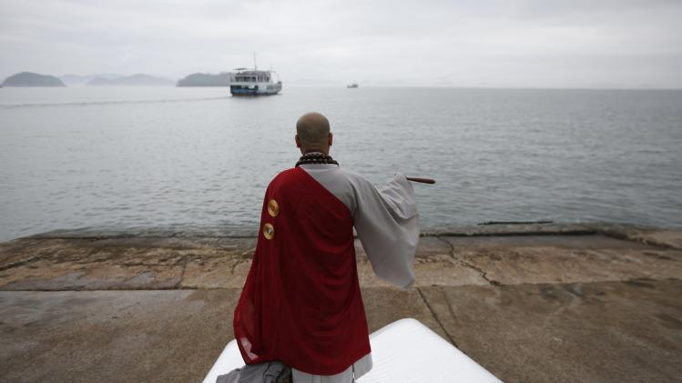 "Buddhist monk prays for missing passengers who were on South Korean ferry ""Sewol"", which sank in sea off Jindo, at a port where family members of missing have gathered, in Jindo"