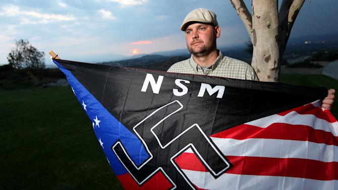FILE - In this Oct. 22, 2010 file photo, Jeff Hall, who was killed by his son, holds a Neo Nazi flag while standing at Sycamore Highlands Park near his home in Riverside, Calif. On Friday Oct. 25, 2013 a judge will to determine where Hall's son will spend his teens and, possibly, his early adult years. The judge hearing the case in Riverside County must decide not how to punish a child for second-degree murder, but how to rehabilitate someone who grew up in an abusive home. (AP Photo/Sandy Huffaker, File)