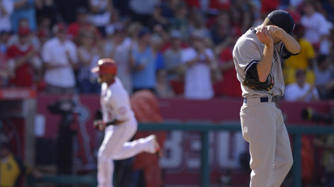 Los Angeles Angels' Erick Aybar, left, rounds third after hitting a solo home run as New York Yankees starting pitcher David Phelps, right, wipes his face during the second inning of their baseball game on Saturday, June 15, 2013, in Anaheim, Calif. (AP Photo/Mark J. Terrill)