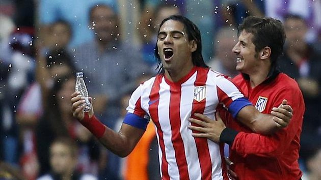 Atletico Madrid's Radamel Falcao (L) celebrates with teammate Cristian Rodriguez after Malaga's Weligton Robson (not seen) scored an own goal during their Spanish first division match at Vicente Calderon stadium (Reuters)