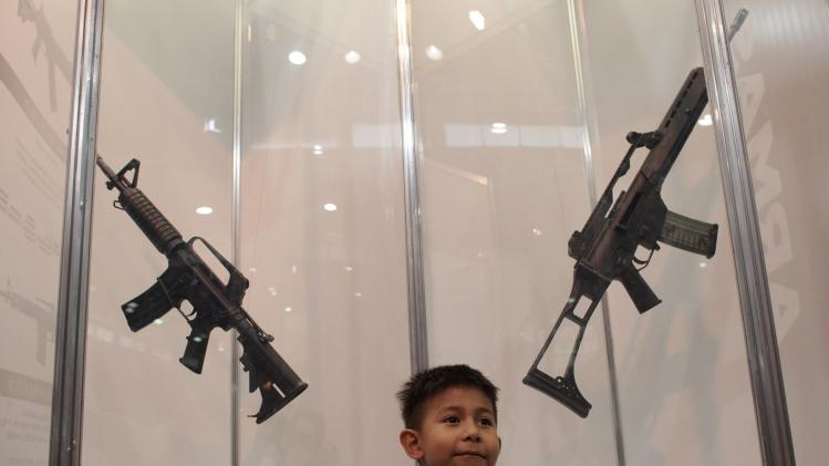 Child stands in front of weapons used by members of the Fuerza Civil (Civil Force) police unit during an exhibition in Monterrey
