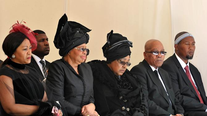 From left: Tobeka Zuma, Nelson Mandela's widow Graca Machel, Winnie Madikizela-Mandela, Nelson Mandela's former wife, South African President Jacob Zuma, and Mandela's grandson Mandla Mandela watch as former South African President Nelson Mandela's casket arrives at his burial site following his funeral service in Qunu, South Africa, Sunday, Dec. 15, 2013. (AP Photo/Elmond Jiyane, GCIS)