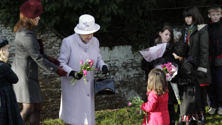 Britain's Queen Elizabeth II, center, receives flowers from children after she and other members of the royal family attended a Christmas Service at St Mary's church in the grounds of Sandringham Estate, the Queen's Norfolk retreat, England, Sunday, Dec. 25, 2011. (AP Photo/Lefteris Pitarakis)