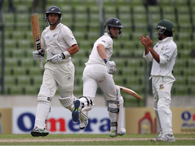 New Zealand's Ross Taylor and Kane Williamson run between the wickets as Bangladesh's Mominul Haque watches, during their second day of second test cricket match of the series in Dhaka