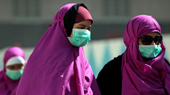 FILE -- In this Tuesday May, 13, 2014 file photo, Muslim pilgrims wear surgical masks to prevent infection from respiratory virus known as the Middle East respiratory syndrome (MERS) in the holy city of Mecca, Saudi Arabia. Saudi which is grappling to contain the spread of a frequently deadly respiratory virus announced Tuesday, June 3, 2014 that a review of the illness led authorities to sharply revise upward the number of confirmed infections and deaths from the disease. A report by the official Saudi Press Agency said authorities have registered a total of 688 confirmed infections and 282 deaths as a result of MERS since the virus was first identified in 2012. (AP Photo/Hasan Jamali, File)