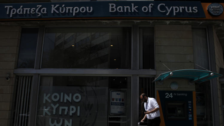 "A man leaves the the ATM machines of a branch of bank of Cyprus in central capital Nicosia, Cyprus, Friday, April 12, 2013. President Nicos Anastasiades said that he will dispatch letters to EU Commission President Jose Manuel Barosso and EU Council chief Herman Van Rompuy telling them of the ""need for a change of EU policy"" toward Cyprus by offering additional assistance. (AP Photo/Petros Karadjias)"