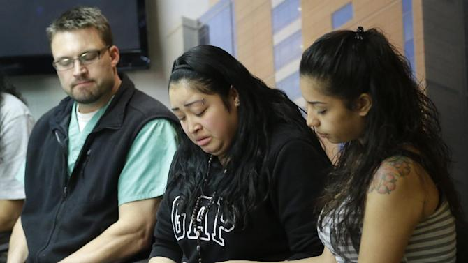 Johana Portillo, center, and her sister Ana Portillo hold hands while Dr. Shawn Smith looks on during a news conference Thursday, May 2, 2013, at Intermountain Medical Center, in Murray, Utah. Ricardo Portillo, a Utah soccer referee, is in a coma after being punched by a teenage player unhappy with one of his calls _ and his family says their only hope is for a miracle. (AP Photo/Rick Bowmer)