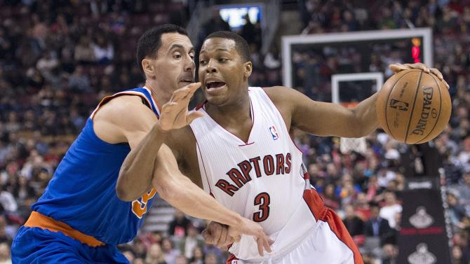 Toronto Raptors guard Kyle Lowry, right, drives past New York Knicks guard Pabblo Prigioni during first half NBA basketball action in Toronto on Friday, March 22, 2013.(AP Photo/The Canadian Press, Nathan Denette)
