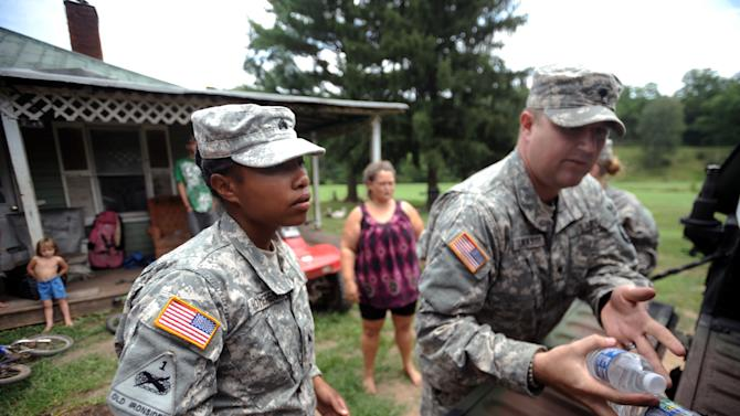 National Guard Sgt. Jessica Homeres, left, and Spc. Jeremy Lemaster, right, deliver food and water to the home of Dewan Dunbar, 40, center, Thursday, July 5, 2012 in Heaters, W.Va. While utility crews continued working to restore power, members of the West Virginia National Guard went door to door with firefighters, police, church groups and others to reach people who were still awaiting help. Residents in the Heaters area have been without power since Friday, June 29, 2012 following a severe storm.  (AP Photo/Jeff Gentner)