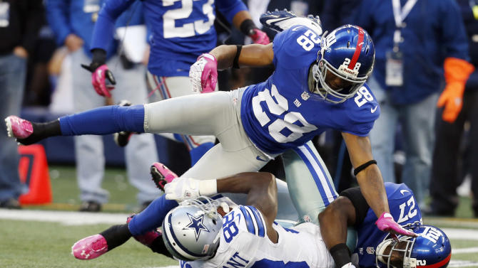 Dallas Cowboys wide receiver Dez Bryant (88) is taken down by New York Giants cornerback Jayron Hosley (28) and Stevie Brown (27) during the first half of an NFL football game Sunday, Oct. 28, 2012 in Arlington, Texas. (AP Photo/Sharon Ellman)