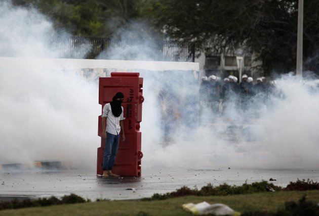A protester takes cover behind a roadblock in the midst of tear gas as riot police officers are seen in the background during clashes in the village of Bani Jamra