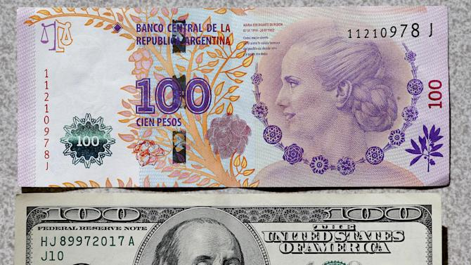 An Argentine 100 pesos bank note is displayed next to the a U.S. 100 dollar note in Buenos Aires