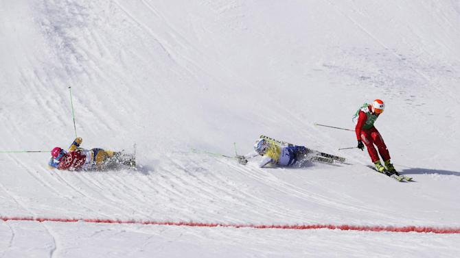 Switzerland's Armin Niederer, right, skis past the crashing  Victor Oehling Norberg of Sweden left, and Russia's Igor Korotkov to win the first men's ski cross quarterinal at the Rosa Khutor Extreme Park, at the 2014 Winter Olympics, Thursday, Feb. 20, 2014, in Krasnaya Polyana, Russia