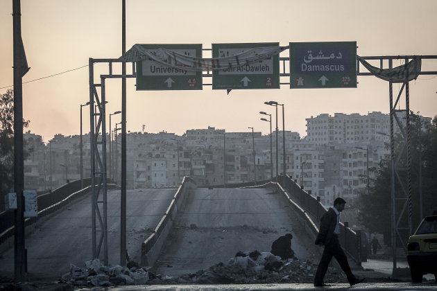 In this Saturday, Oct. 27, 2012 photo, a Syrian resident walks at sunset through a crossroad in downtown as mortar explosions, not seen, sound in the distance, in the Saif al-Dawleh, neighborhood, Aleppo, Syria. (AP Photo/Narciso Contreras).
