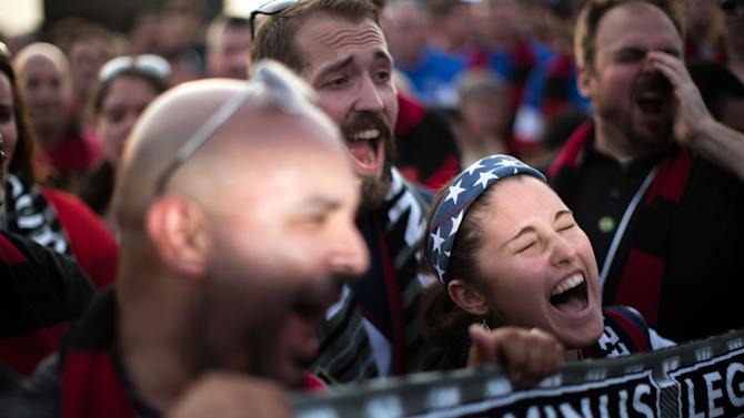 Light shines on the faces of Jorge Alonso, left, and Kelly Carter, right, as they cheer during a party at which Atlanta United FC was announced as the name of an MLS soccer expansion team, Tuesday, July 7, 2015, in Atlanta. The team is scheduled to begin to play in 2017 at the city's new retractable-roof stadium. (AP Photo/Branden Camp)