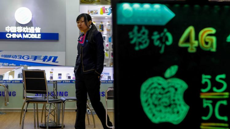 A sales assistant walks inside a China Mobile store in Guangzhou