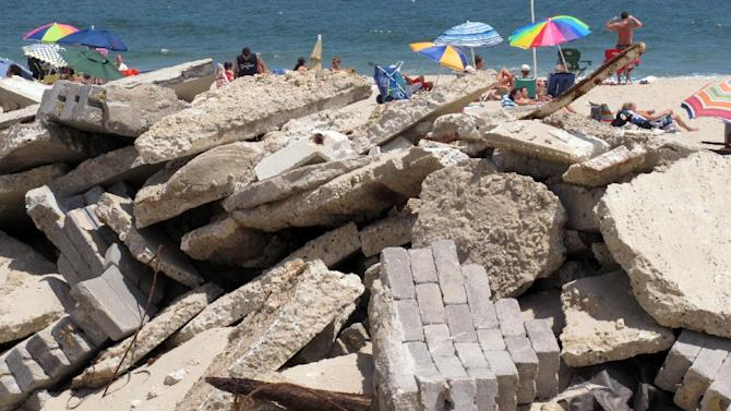 In this July 5, 2013 photo, rubble from a beachfront home still sits on the sand in Point Pleasant Beach, N.J., as beachgoers spend time closer to the water. A wave of large property tax increases that had been feared in the aftermath of Superstorm Sandy has not materialized thanks to large amounts of federal aid, borrowing by towns, and the use of rainy-day surplus funds. (AP Photo/Wayne Parry)
